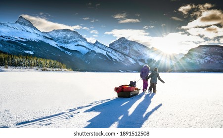 Two children drag a sled full of ice fishing gear across frozen ice and snow on the Spray Lakes in Peter Lougheed Provincial Park in the Canadian Rockies.