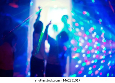 Two children are drawn to light. Hope for healing. Children at party with laser show with colorful rays lighting and neon in blue LED lights room at birthday or Christmas. Blured with selective focus
