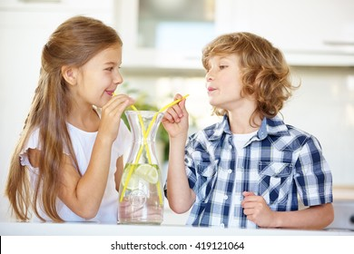 Two children drinking fresh water with straw in the kitchen