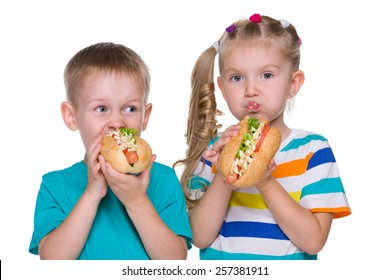 Two children eat hot dogs on the white background