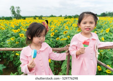 Two children eat icecream at sunflowers field in a sunny day,bright sunlight,cute girl,dress pink