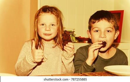 Two children are eating brown cookies Girl is giving thumb up.  Funny and children concept. Add warm effect
