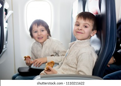 Two children, eating sandwiches on board in aricraft, traveling on vacation with paretns