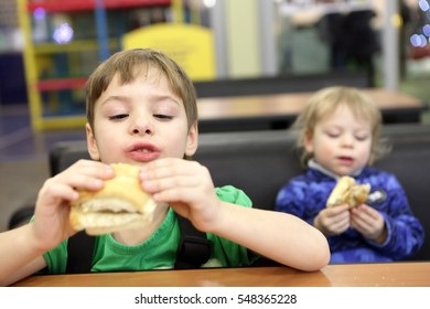 Two children eating sandwiches at table in cafe