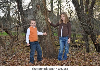 two children enjoy an autumn day in the woods