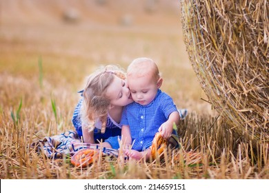 Two children, funny toddler girl and a little baby boy, playing in a field with hay rolls eating pretzels during Oktoberfest in Germany. Sister kissing and hugging her little brother