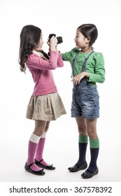 Two children girl(female, woman) hold a camera take a picture each other(together) with smile(happy) for sons(instagram) isolated white at the studio.