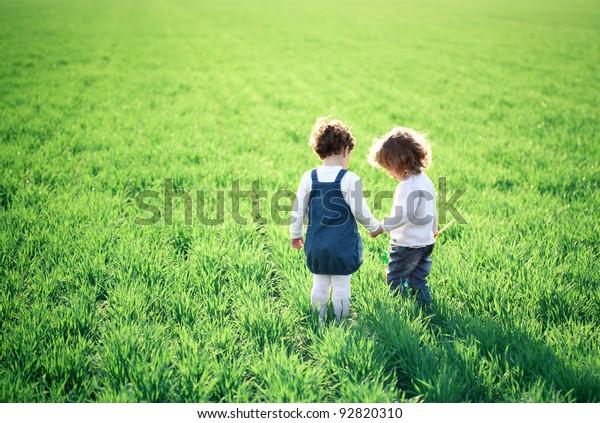 Zwei Kinder gehen auf grünem Feld im Frühling