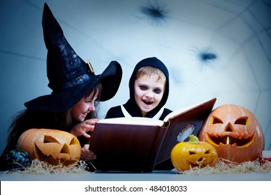 Two children in Halloween costumes reading a book among pumpkins and smiling