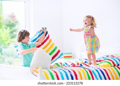 Two children, happy laughing boy and cute curly little girl having fun at pillow fight with feathers in the air jumping, laughing in a white bedroom with colorful bedding. Focus on jumping girl.