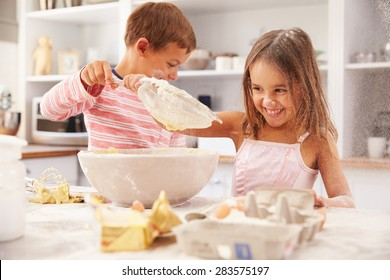 Two children having fun baking in the kitchen