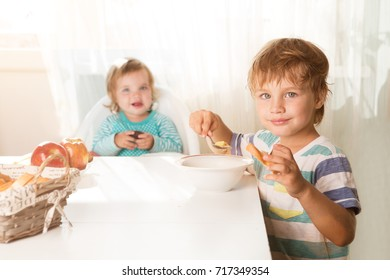 Two children having for lunch soup at home. healthy food.
