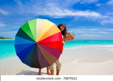 Two children hiding behind a colorful umbrella on the beach