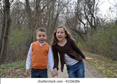two children hold hands while on a walk in autumn