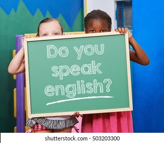 "Two children holding a chalkboard saying ""Do you speak english?"" in preschool"