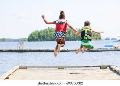 Two children are holding hands, jumping off a wooden dock into the lake water. They are wearing life jackets. There is one girl and one boy holding hands as they plunge into the water.