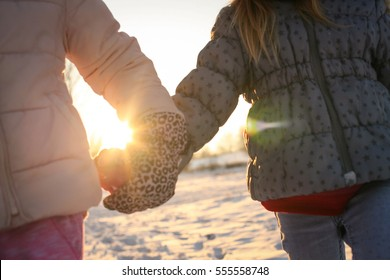 Two children holding hands outdoor.