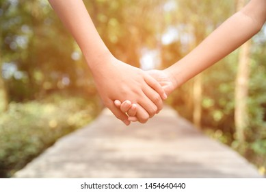 Two children holding hands together on the wooden way and natural background in the morning. Friendship Day, Best Friend concept.