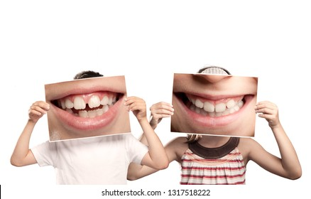two children holding a picture of a mouth smiling isolated on white
