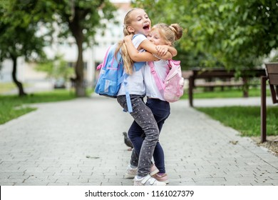 Two children hug and laugh. The concept of school, study, education, friendship, childhood