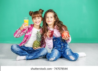 Two children with juice and fruit. Girls with pineapple and pomegranate. The concept of a healthy lifestyle, food, childhood, vitamins, vegetarianism.