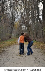 two children kiss while on a walk in autumn
