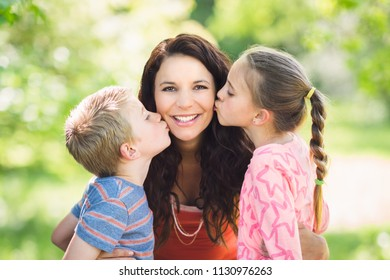 Two children kissing mother on cheek