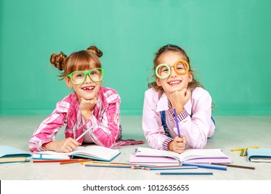 Two children laugh and read in glasses. The concept of childhood, learning, friendship, family, school, lifestyle.