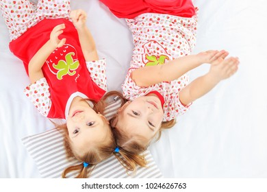 Two children laughing and lying in pajamas. The concept of childhood, lifestyle, morning.