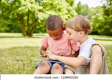 Two children learning with game in tablet computer and having fun as team