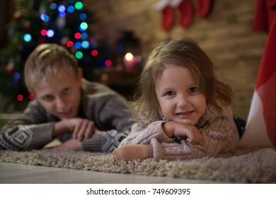 Two children lie on the floor near a Christmas tree, happy Christmas! Brother and sister meet at home christmas