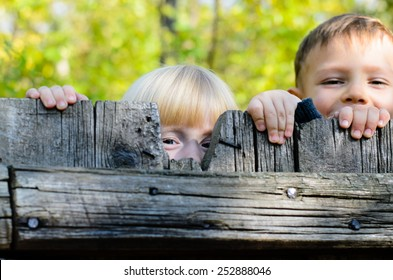 Two children, a little blond girl and boy, standing side by side peeking over an old rustic wooden fence with just their eyes visible