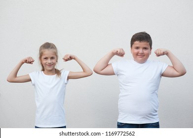a231eaf8c9943 two children little thin girl and thick boy showing their muscle on  copyspace background