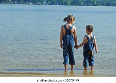 two children look out over the water while wearing their overalls