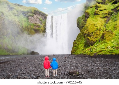 Two children looking at majestic Skogafoss waterfall in Iceland
