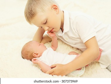 Two children lying on the bed, eldest brother hugging youngest baby