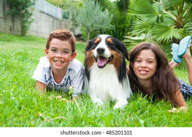 Two children lying on grass with a dog