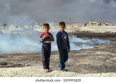 Two children near an oil well set on fire by the ISIS to slow down the coalition's advance, the fire was extinguished.