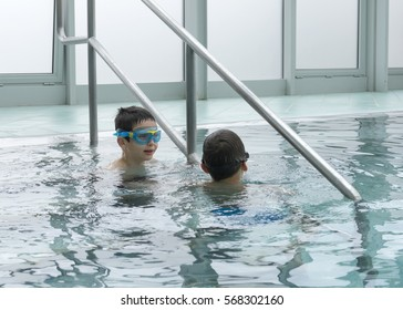 Two children on the edge of indoor swimming pool.