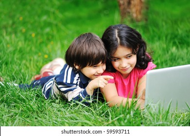 Two children on meadow with laptop