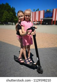Two children on scooters in city