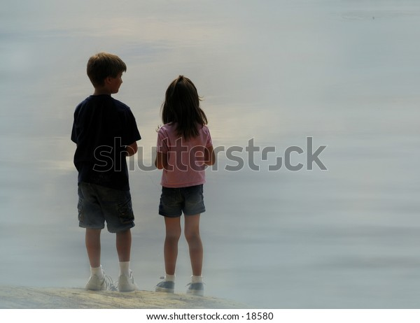 two children on the shore of a misty lake