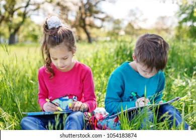 Two children are painted in the park. Guy and girl. Concept of education, education, childhood, lifestyle.