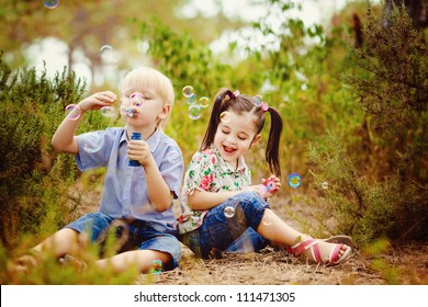 Two children in the park blowing soap bubbles and having fun
