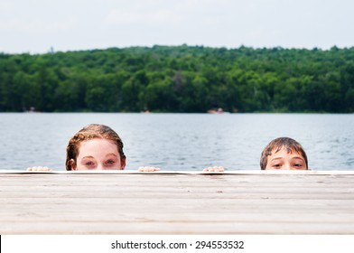 two children peeking over a dock in a lake