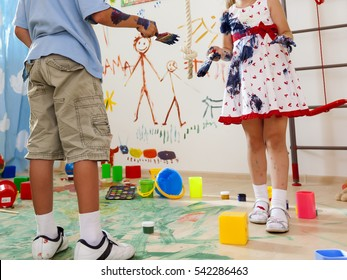two children play paint brush colors on the wall in the room