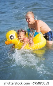 Two children play in the water of the sea