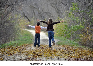 two children playfully run down a tree lined path on a beautiful autumn day