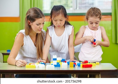 Two children playing with building blocks in kindergarten with a nursery teacher helping