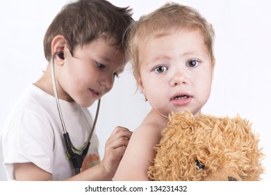 Two children playing doctor with a red stethoscope and a teddy bear isolated on white